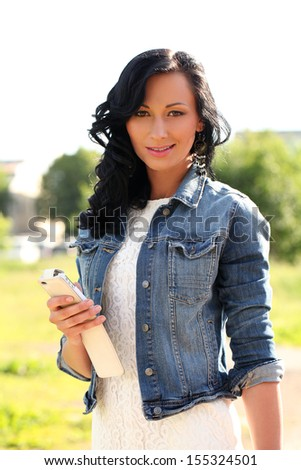 Beautiful caucasian woman with mobile phone outdoors at sunny day