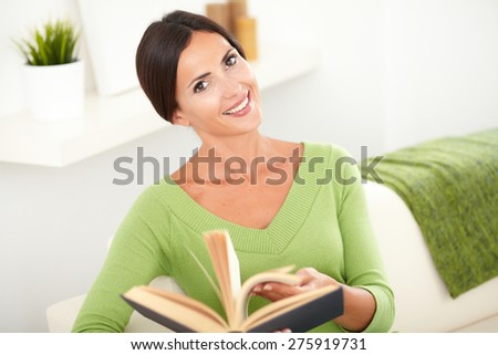Beautiful caucasian woman with straight hair browsing a book while looking at the camera - stock photo