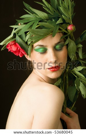 Beautiful caucasian woman with wreath of flowers around her head. Closed her eyes and green make up - stock photo