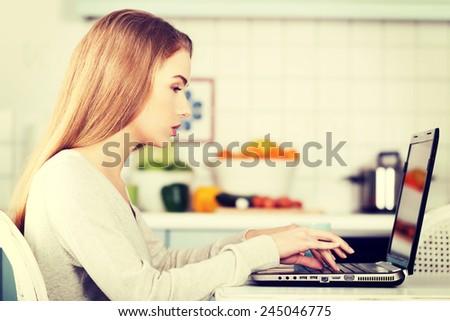Beautiful caucasian woman working on laptop in kitchen. - stock photo