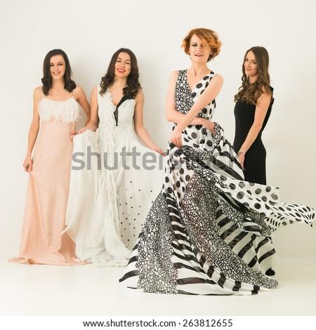 beautiful caucasian women in cocktail dresses posing together, dancing and having fun - stock photo