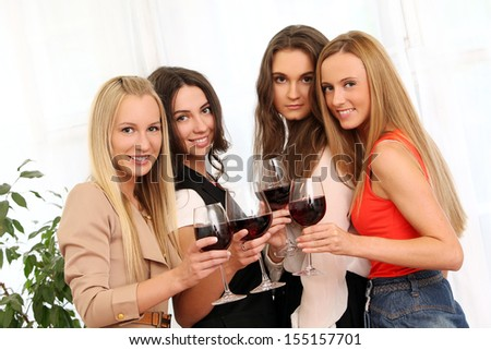 Beautiful caucasian women with red wine celebrating at home