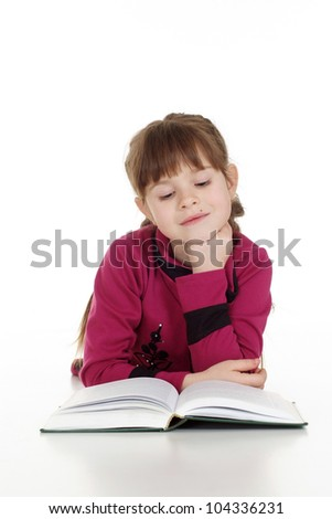 Beautiful Caucasian young girl lying with a book on a white background