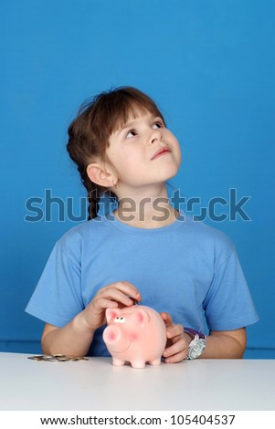 Beautiful Caucasian young girl sitting at a table with a piggy bank on a blue background