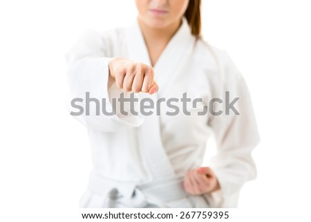 Beautiful caucasian, young, woman performing karate moves on white background