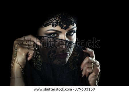 Beautiful caucasian young woman with black veil on face, fancy arabian costume - stock photo