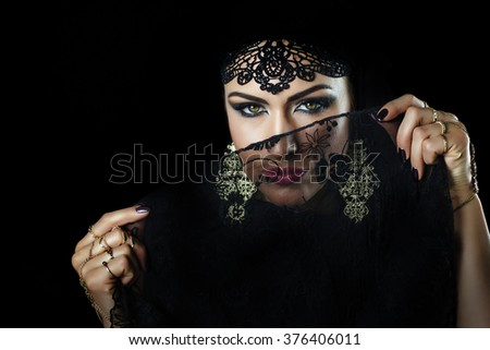 Beautiful caucasian young woman with black veil on face, fency arabian costume - stock photo