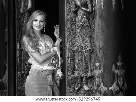 Beautiful caucasian young woman with blond hair wear traditional thai dress, with garland in hand, standing and smiling in front of vintage door of temple. Black and white image