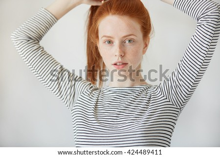 Beautiful Caucasian young woman with healthy freckled skin looking and smiling with thoughtful expression at the camera. Redhead girl wearing striped top posing iolated against white concrete wall  - stock photo