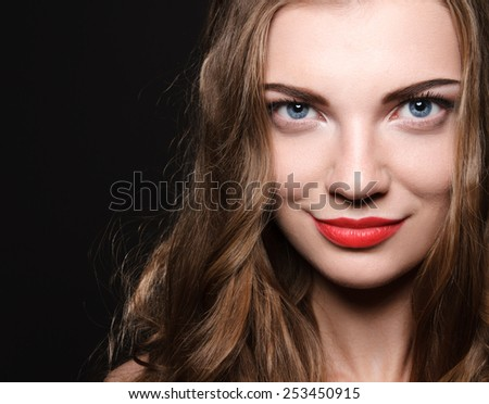 Beautiful caucasian young woman with red lips make up and curl hairs looking at camera. High resolution studio head shot - stock photo