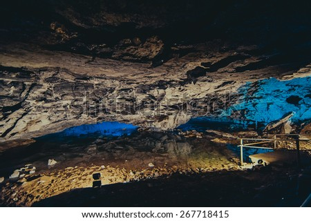 Beautiful cave with color light lake underground - stock photo