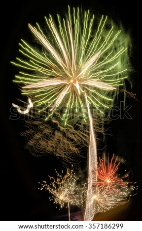 Beautiful celebratory fireworks in the night sky red and orange flowers looking like