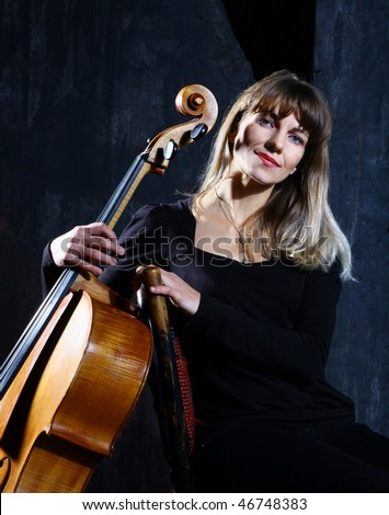 Beautiful cello musician on grey wall background