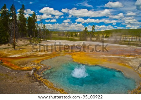Beautiful cerulean geyser surrounded by colorful layers of bacteria, against cloudy blue sky. - stock photo