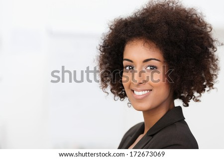 Beautiful charming African American woman with a lovely warm smile and frizzy afro hairstyle, closeup face portrait with copyspace