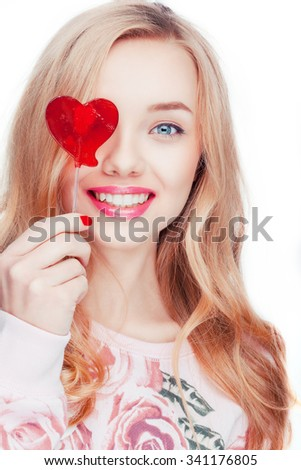 Beautiful charming attractive blonde model posing in the studio looking at camera taking a candy like a red heart. happy face expression.  - stock photo