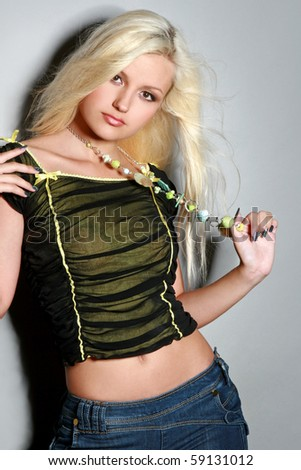 Beautiful, charming blonde girl, poses on a grey background with a beads in hands - stock photo