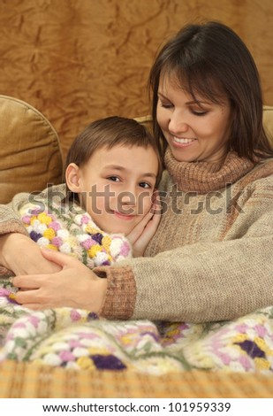 Beautiful charming Caucasian mama with her son on a brown background
