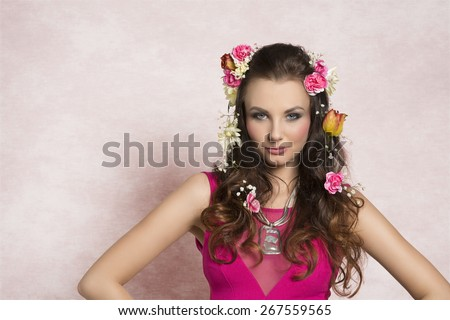 Beautiful, charming, fresh brunette woman with curly hairstyle with spring flowers. She is wearing pink dress with transparent part and silver necklace. - stock photo
