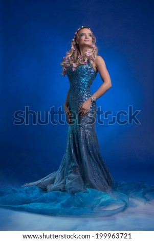 Beautiful charming mermaid against blue background smiling mysterious