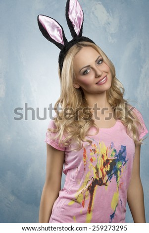 Beautiful, charming, smiling woman with blonde, curly hair and rabbit ears, wearing pink t-shirt and nice dark make up. - stock photo