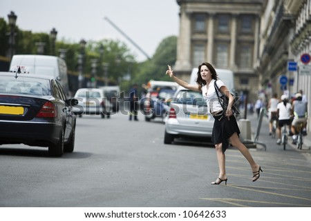 beautiful charming woman hailing a taxi cab in the street of paris france - stock photo