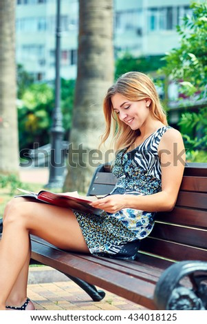 Beautiful charming woman sitting on bench in the park and reading magazine. Outdoors.