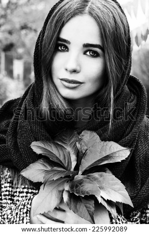 beautiful charming young attractive girl with large blue eyes with a handkerchief on his head, long dark hair holding a fall bouquet of leaves on a cold autumn day - stock photo