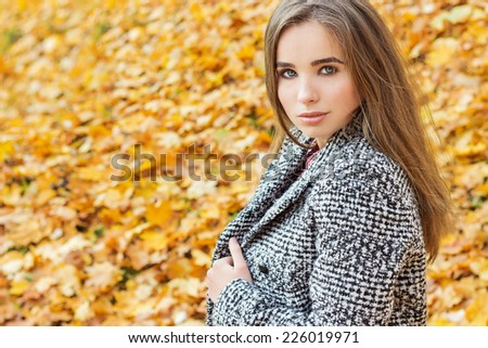beautiful charming young attractive girl with large blue eyes, with long dark hair in the autumn forest in coat - stock photo