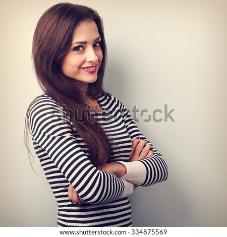 Beautiful charming young casual woman with folded hands looking happy. Vintage portrait - stock photo