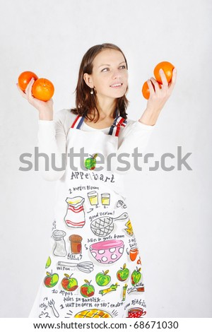Beautiful cheerfu Woman holding oranges - stock photo
