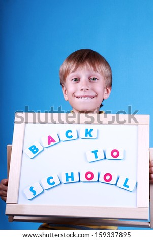 """Beautiful cheerful blond boy smiles happily holding a small blackboard with a message """"Back to school"""" - stock photo"""