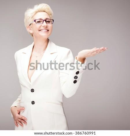 Beautiful cheerful blonde woman with short hairstyle wearing elegant costume, posing in studio. - stock photo