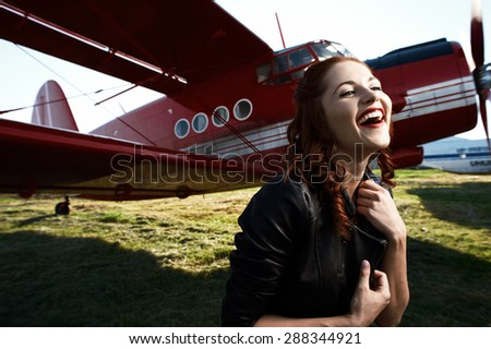 beautiful cheerful brown haired pin-up lady with vintage haircut and red dress and black jacket stands against airplane in setting sun. The airplane is red and vintage and stands on sunlit grass.  - stock photo