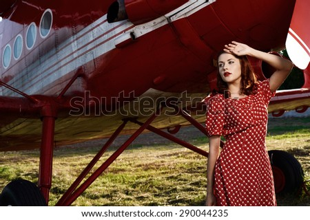 beautiful cheerful brown haired pin-up lady with vintage haircut and red dress stands against airplane in setting sun. The airplane is red and vintage and stands on sunlit grass.  - stock photo
