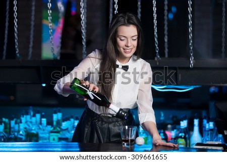 Beautiful cheerful brunette bartender girl in white shirt and black bow tie, serving alcohol drink at nightclub bar, holding bottle in hand, pouring drink in glass - stock photo