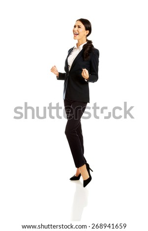 Beautiful cheerful businesswoman in a winner gesture. - stock photo