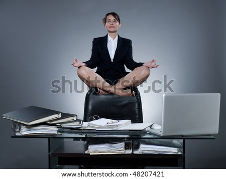 beautiful cheerful caucasian  business woman levitate from her desk on isolated background - stock photo