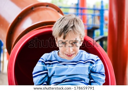 Beautiful cheerful child playing on a colorful playground smiling looking into the camera - stock photo