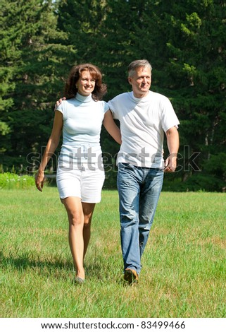 Beautiful cheerful couple walking in summer park - stock photo