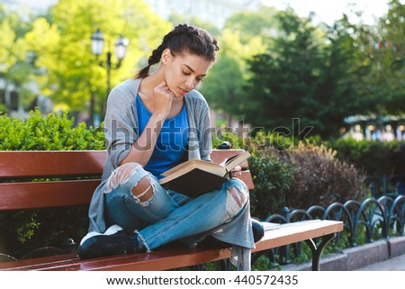 Beautiful cheerful dark skinned girl reading the magazine at the nature background and sits on a bench.