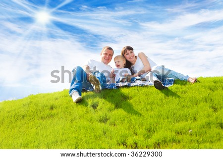 Beautiful cheerful family sitting on the green hill - stock photo