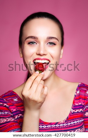 beautiful cheerful girl eating strawberries. the concept of fun and healthy food. pink background - stock photo