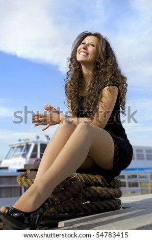 beautiful cheerful girl has a rest on landing stage - stock photo