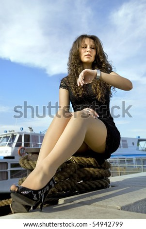 beautiful cheerful girl looks at watch on her hand, landing stage - stock photo