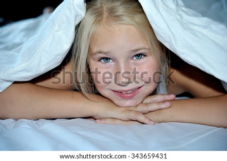 Beautiful cheerful girl looks out from under white  blanket - stock photo