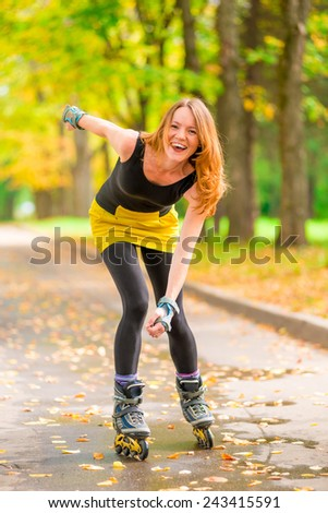 beautiful cheerful girl roller skate active in the autumn park - stock photo