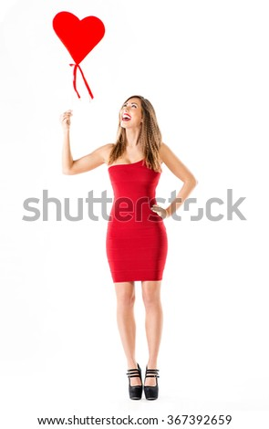 Beautiful cheerful girl standing and holding red heart.