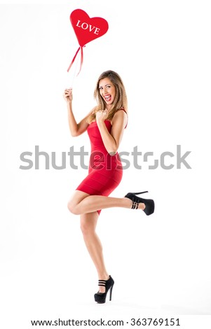 Beautiful cheerful girl standing and holding red heart. Looking at camera.