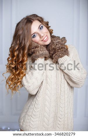 Beautiful cheerful girl with amazing smile in a warm sweater and mittens - stock photo